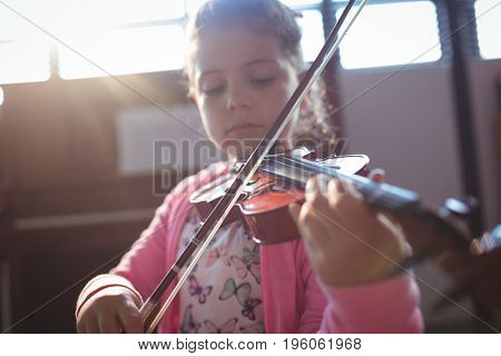 Girl student rehearsing violin in music class