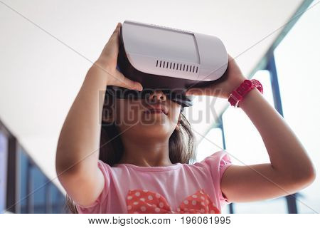 Low angle view of girl using virtual reality glasses against ceiling in corridor at school