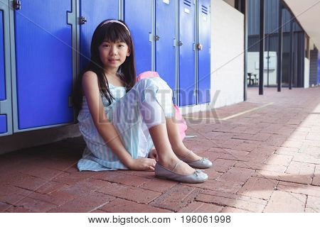 Portrait of schoolgirl sitting on pavement by lockers at school