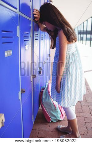 Full length of sad girl leaning on lockers in corridor at school