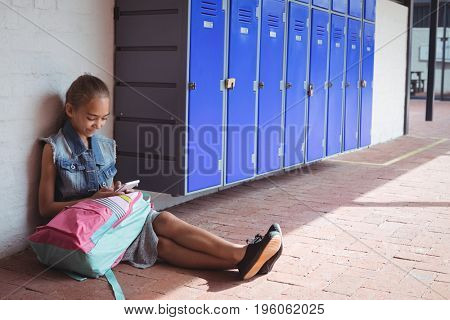 High angle view of elementary student using mobile phone while sitting on pavement by lockers at school