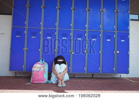 Schoolgirl sitting on pavement by lockers in corridor at school