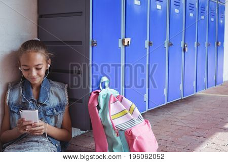 Elementary student listening music through headphones while using smartphone by lockers at school