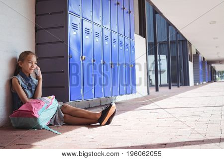 Elementary student talking on mobile phone while sitting by lockers at school