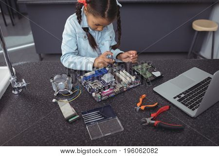 High angle view of concentrated elementary girl assembling circuit board on desk at electronics lab