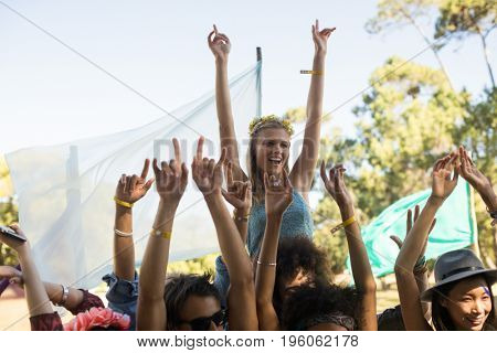 Happy woman by fans with arms raised enjoying at music festival