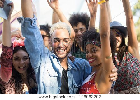 Portrait of happy friends with arms raised enjoying during music festival
