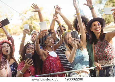 Smiling friends taking selfie through their mobile phones while enjoying at music festival