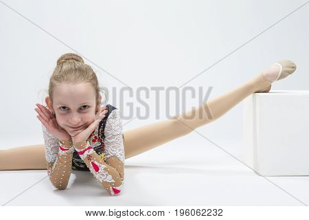 Young Caucasian Female Rhythmic Gymnast Athlete In Professional Competitive Suit Doing Split Exercise While Posing in Studio Against White. Horizontal Image Orientation