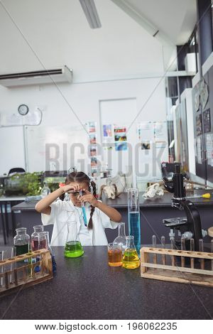 Elementary student doing scientific experiment with blue chemical at science laboratory