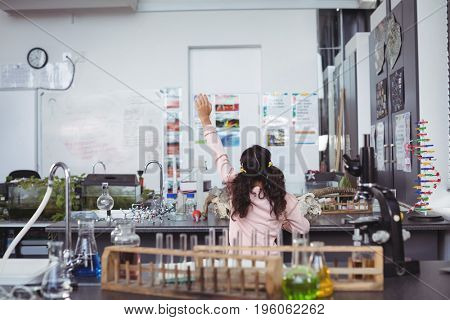 Rear view of elementary student raising hand by desk at science laboratory
