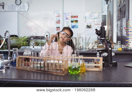 Elementary schoolgirl holding test tube by desk at science laboratory