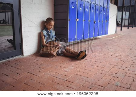 Full length of elementary student using mobile phone while sitting on pavement by lockers at school