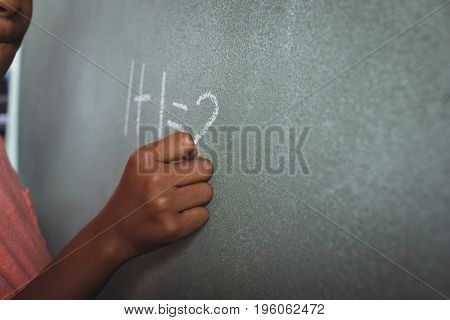 Cropped image of student writing on blackboard in classroom