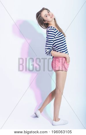 Youth Lifestyle Concepts and Ideas. Full Length Portrait of Smiling Happy Caucasian Brunette Girl in Striped Shirt and Pink Shorts. Standing Half Turned Backwards Against White. Vertical Image