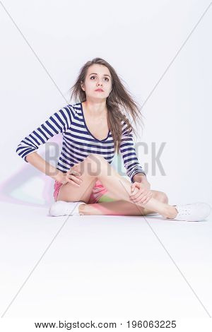 Portrait of Caucasian Brunette Girl in Striped Shirt and Pink Shorts. Sitting On Floor with Crossed Legs. Against White. Vertical Image Composition