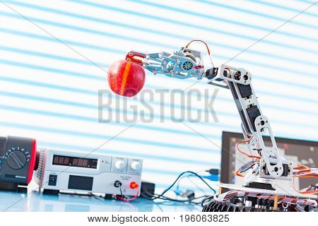 robot holds an apple  in his arm