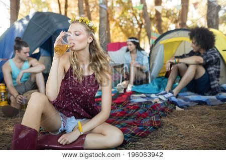 Young woman drinking beer while sitting with friends at campsite