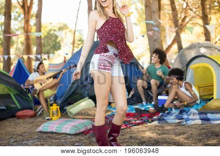 Young woman standing on field with friends sitting by tents in background at campsite