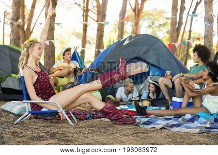 Happy woman sitting on chair with friends by tent at campsite