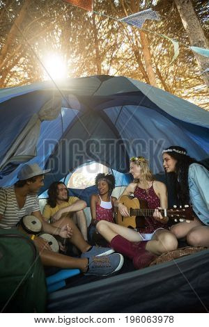 Happy young friends enjoying while sitting together in tent on sunny day
