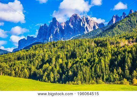 Warm autumn in the Dolomites, the Val de Funes. The valley is surrounded by a dentate wall of dolomite rocks. The concept of ecological tourism