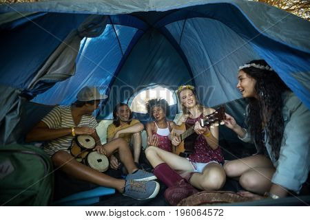 Happy young friends enjoying while sitting together in tent