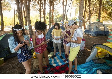 Friends using mobile phones while standing on field at campsite