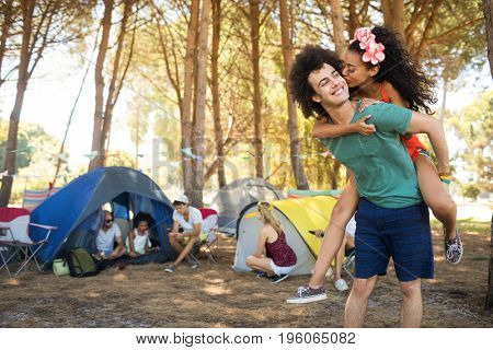 Woman kissing man piggybacking while standing at campsite