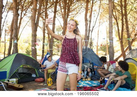 Smiling woman taking selfie while standing on field at campsite