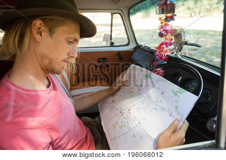 Close-up of man reading map while sitting in camper van