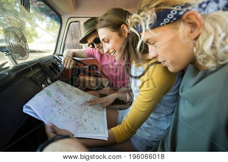 Smiling friends reading map while sitting in camper van