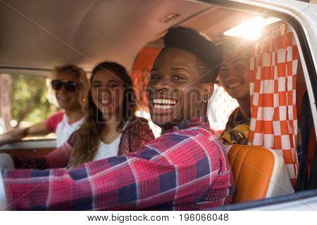 Portrait of cheerful friends sitting in camper van