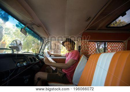 Portrait of man with map sitting in camper van