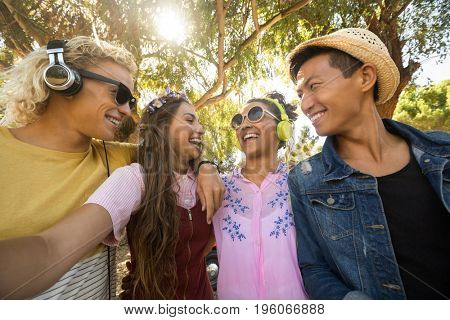 Close-up of smiling friends standing side by side against trees on sunny day