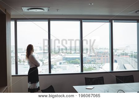 Side view of businesswoman looking out through glass window while standing at office