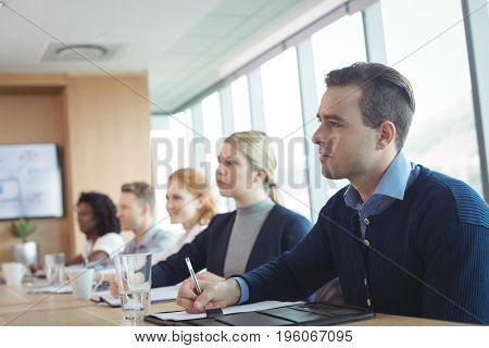 Concentrated business people sitting at conference table during meeting in board room