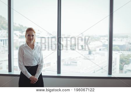 Portrait of young businesswoman standing against glass windows at office