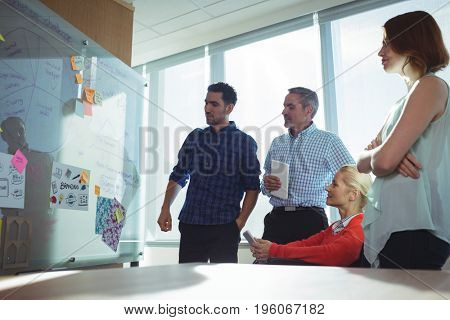 Thoughtful business colleagues looking at whiteboard in office during sunny day