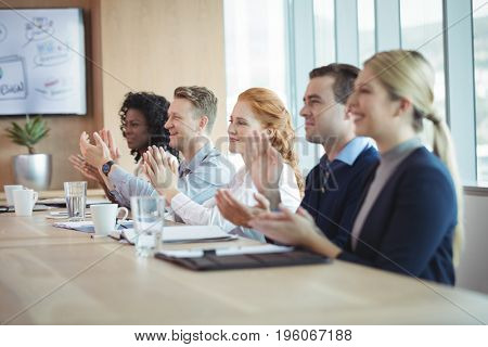 Happy business people clapping at conference table during meeting in board room