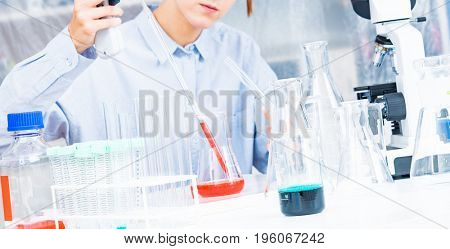 Woman Scientist Adding Liquid To Test Tube With Pipette In Lab