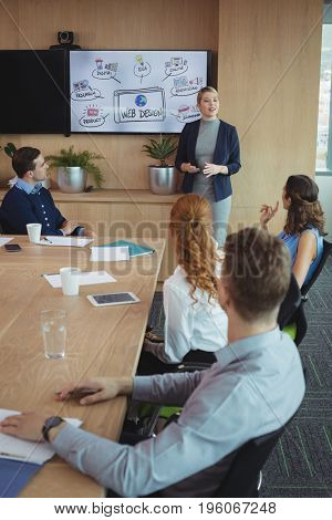 Young businesswoman discussing with colleagues during meeting in board room