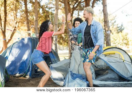 Happy young friends giving high five while setting up tent at countryside