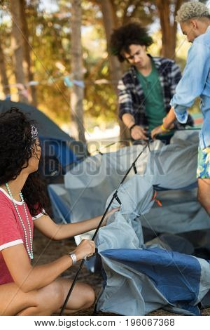 Young woman with male friends setting up tent at campsite