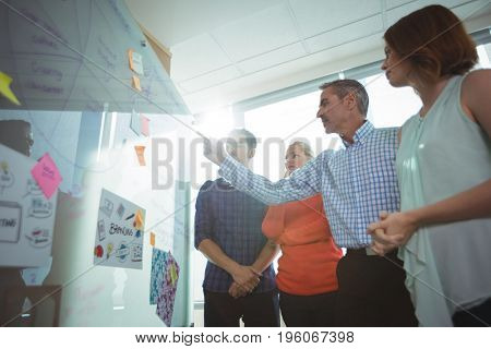 Low angle view of business people discussing over whiteboard at office during sunny day