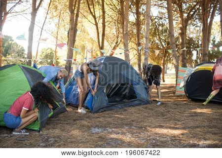 Friends setting up their tents together on field at countryside