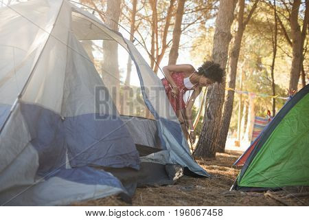 Young woman setting up tent on field at countryside