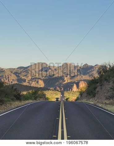 Arizona desert highway leading red to red rock Superstition Mountain are in Tonto National Park near Phoenix.