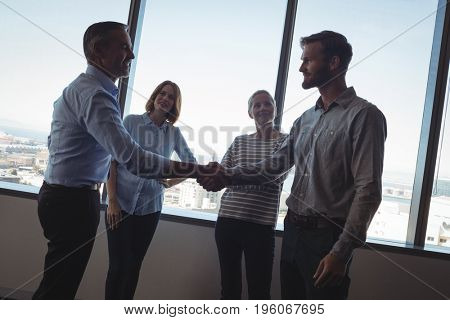 Business people shaking hands against glass windows at office