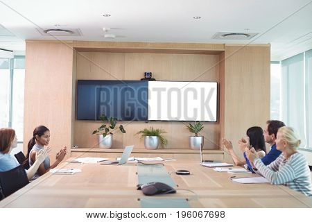Business people clapping during meeting in board room